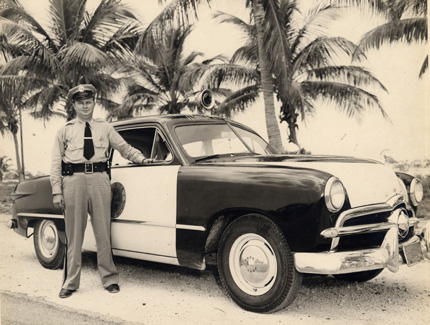 A Florida Highway Patrol Officer and his car in Key West C 1950. Monroe County Library Collection.